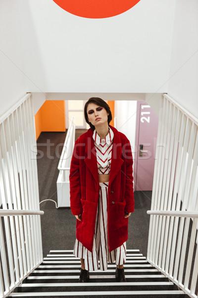 Nő piros kabát áll lépcsősor elegáns Stock fotó © deandrobot