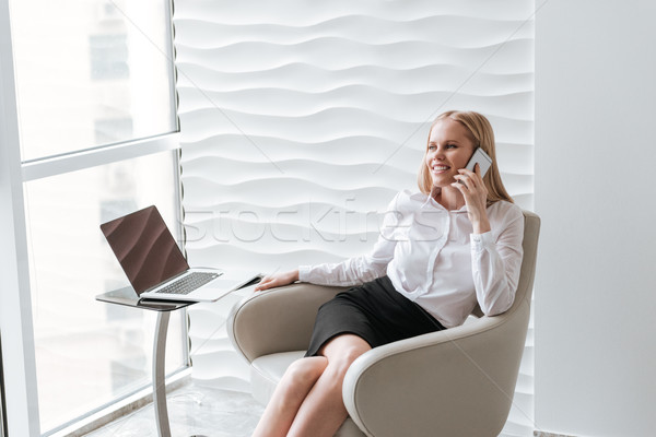 Business lady sitting in office on chair. Talking by phone. Stock photo © deandrobot
