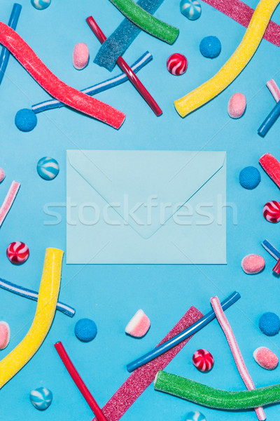 Top view of colorful sugar candies and lollies with envelope Stock photo © deandrobot