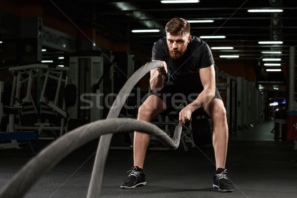 Young strong sports man make sport exercises in gym Stock photo © deandrobot