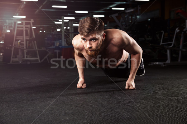Concentrated handsome young strong sports man make plank exercise Stock photo © deandrobot