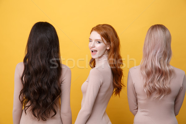 Redhead lady winking near blonde and brunette women Stock photo © deandrobot