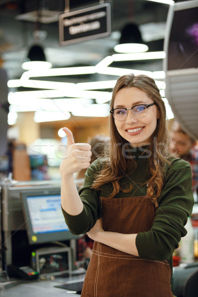 Happy cashier woman on workspace showing thumbs up. Stock photo © deandrobot