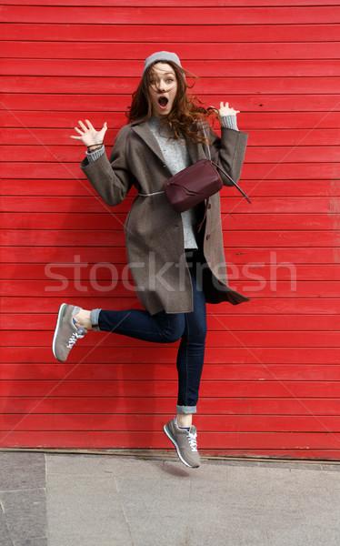 Engraçado maravilhado mulher jovem saltando ar vermelho Foto stock © deandrobot
