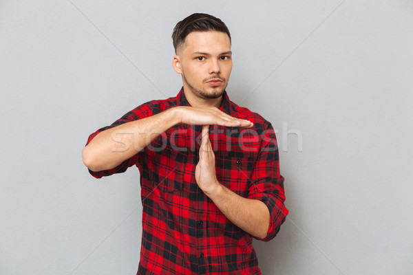 Serious man showing time-out gesture Stock photo © deandrobot