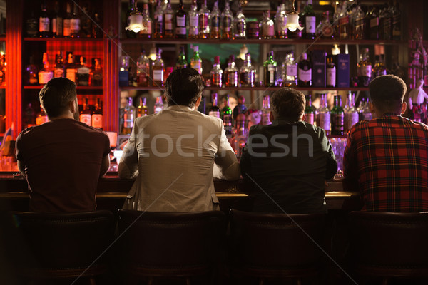 Back view of four young men drinking beer Stock photo © deandrobot