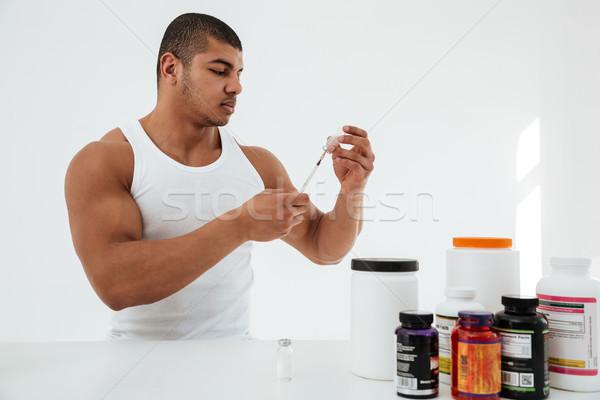 Sportsman standing over white background holding syringle Stock photo © deandrobot