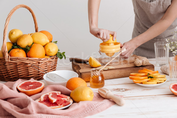 Cropped picture of woman squeezes out juice of a citruses. Stock photo © deandrobot