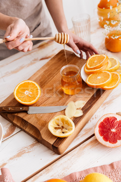 Woman standing near table with citruses and holding honey. Stock photo © deandrobot