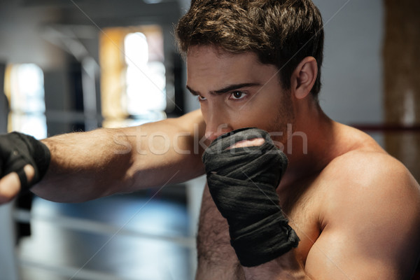 Young strong man training in gym Stock photo © deandrobot