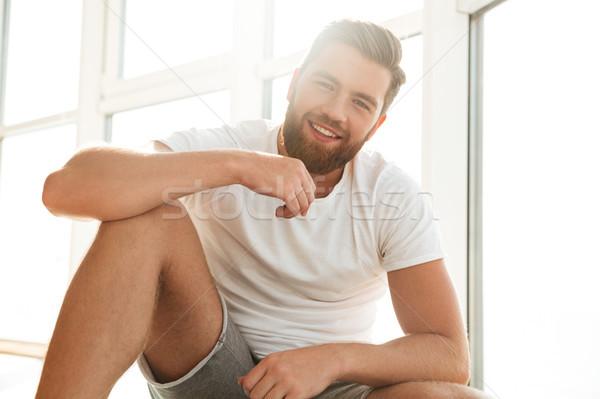 Glimlachend knap bebaarde man venster home Stockfoto © deandrobot