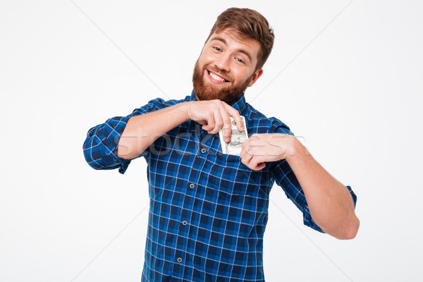 Pleased Smiling bearded man in checkered shirt puts a money Stock photo © deandrobot
