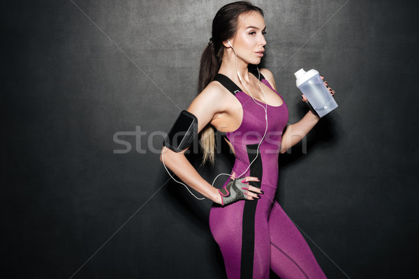 Woman with bottle and case for phone listening music Stock photo © deandrobot