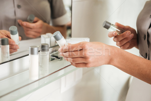 Young hotel maid putting bath accessories in a bathroom Stock photo © deandrobot