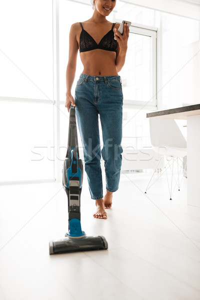Cropped image of a woman in jeans vacuuming the floor Stock photo © deandrobot