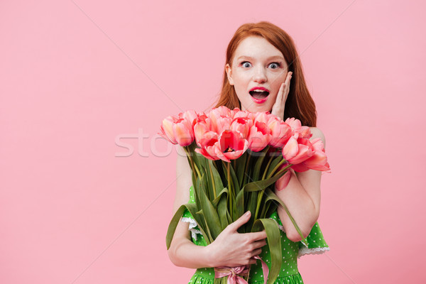 Surprised woman holding bouquet Stock photo © deandrobot