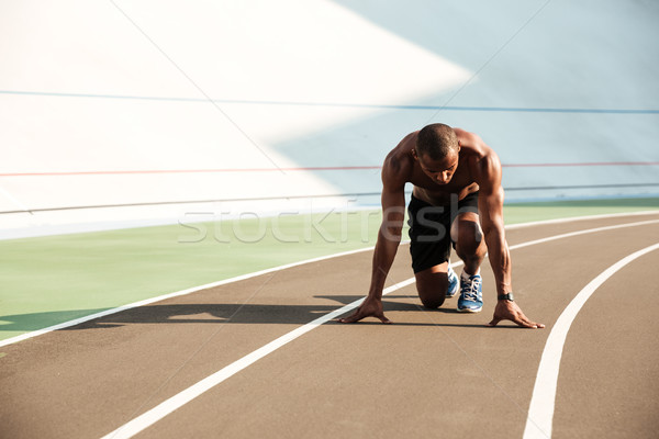 Young afro american sports man in starting position ready to sta Stock photo © deandrobot