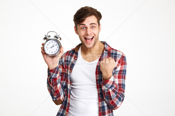 Portrait of a happy satisfied man holding alarm clock Stock photo © deandrobot