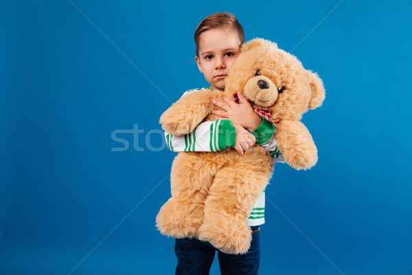 Higgadt fiatal srác ölel plüssmaci néz kamera Stock fotó © deandrobot