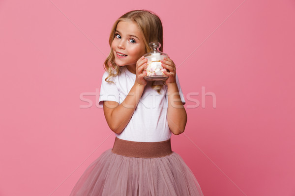 Portrait of a pretty little girl holding jar of marshmallow Stock photo © deandrobot