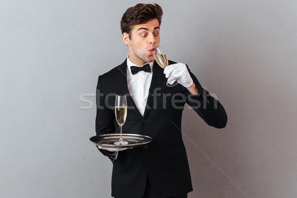 Funny jóvenes camarero potable champán imagen Foto stock © deandrobot