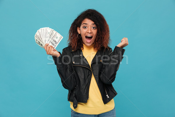 Surprised happy african woman in leather jacket holding money Stock photo © deandrobot