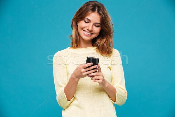 微笑的女人 毛線衣 寫作 信息 智能手機 藍色 商業照片 © deandrobot