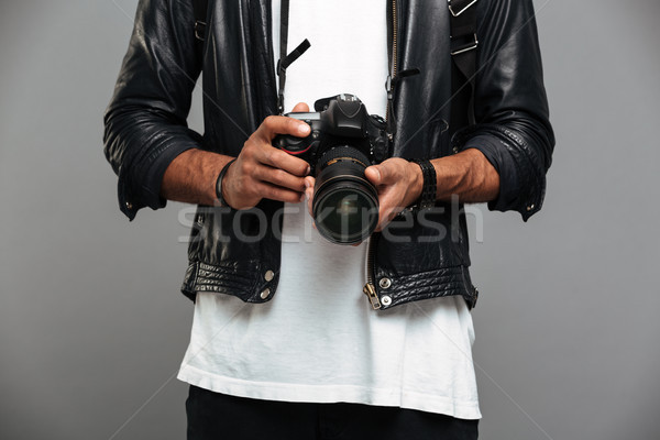 Cropped photo of stylish afro american guy holding digital camer Stock photo © deandrobot