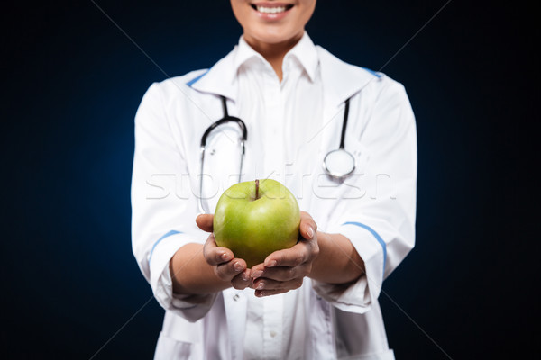 Cropped photo of young woman in medical gown holding green apple Stock photo © deandrobot