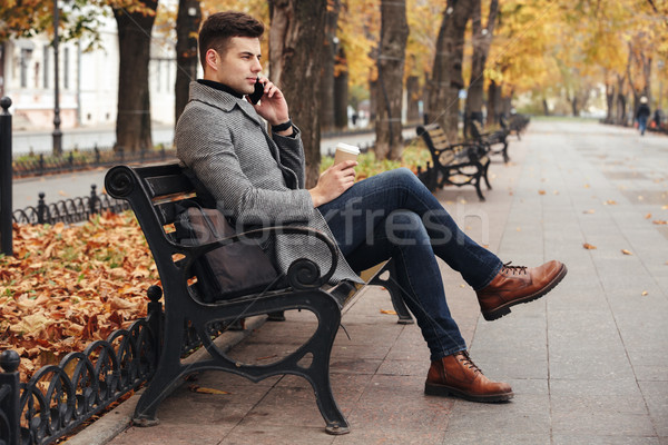 Picture of elegant brunette male in coat and jeans drinking take Stock photo © deandrobot