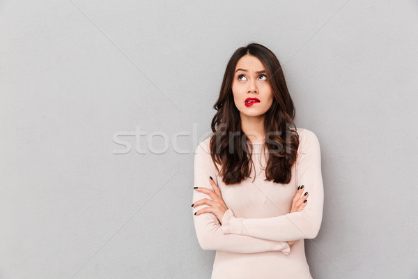 Portrait of young woman biting her red lips standing with arms f Stock photo © deandrobot