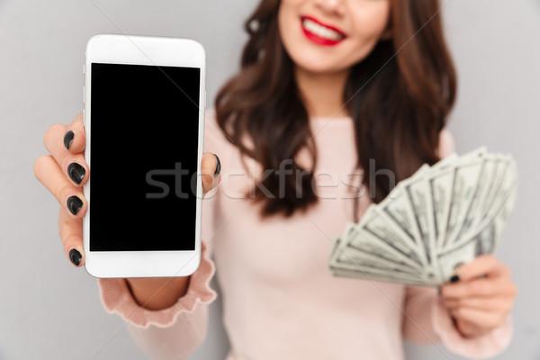 Cropped portrait of brunette female 30s showing fan of money dol Stock photo © deandrobot
