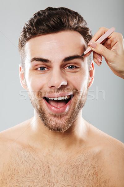 Portrait of joyful man smiling while female hand plucking his ey Stock photo © deandrobot