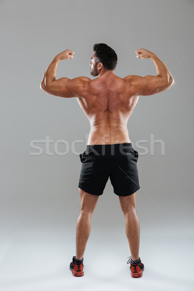 Back view full length portrait of a shirtless male bodybuilder Stock photo © deandrobot