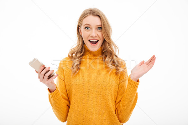 Surprised young woman using mobile phone. Stock photo © deandrobot
