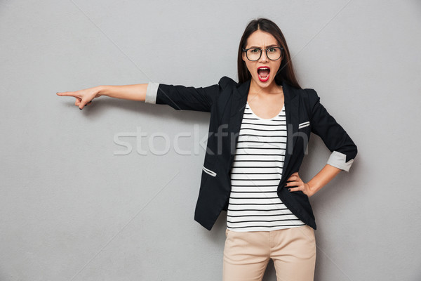 Angry asian business woman in eyeglasses with arm on hip Stock photo © deandrobot