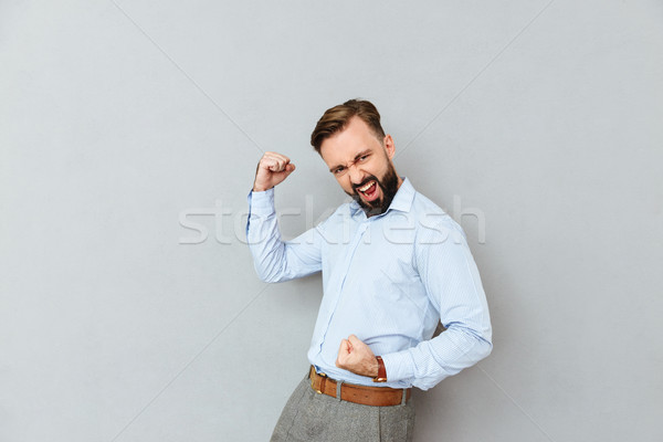 Happy bearded man in business clothes rejoice Stock photo © deandrobot