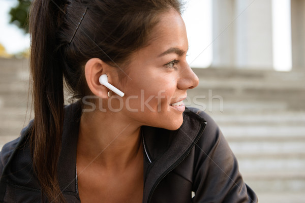 Close up portrait of a smiling fitness woman in earphones Stock photo © deandrobot