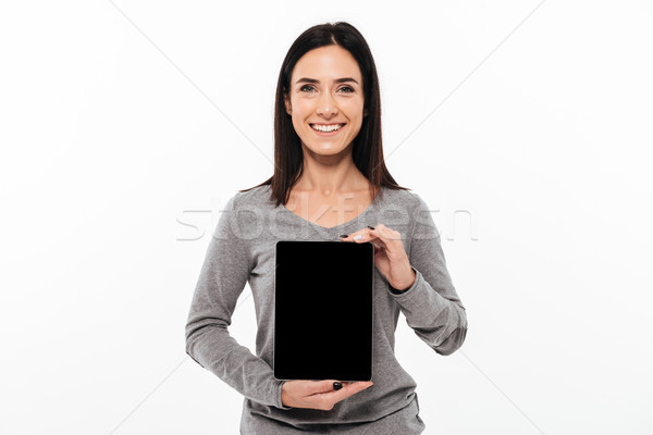Young cheerful lady showing display of tablet computer. Stock photo © deandrobot