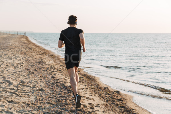 Back view of young sportsman jogging at the beach Stock photo © deandrobot