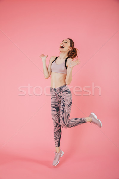 Full length image of Screaming sportswoman jumping and rejoices Stock photo © deandrobot