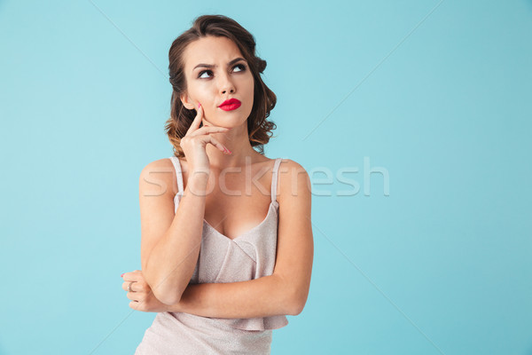 Pensive brunette woman in dress touching chin and looking away Stock photo © deandrobot