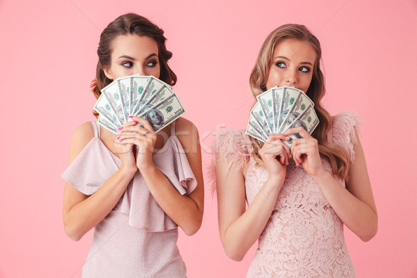 Two successful girls 20s in stylish dresses covering face with f Stock photo © deandrobot