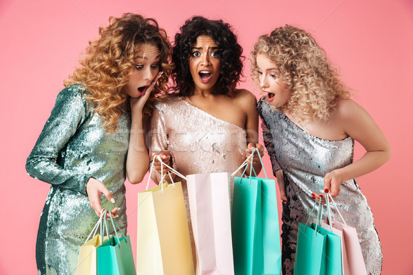 Stock photo: Three beautiful shocked women in shiny dresses