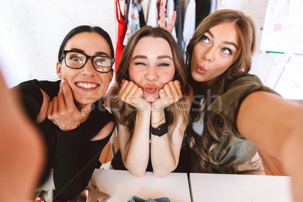 Three lovely young women clothes designers Stock photo © deandrobot