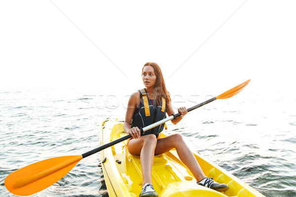 Beautiful woman kayaking on lake sea in boat. Stock photo © deandrobot
