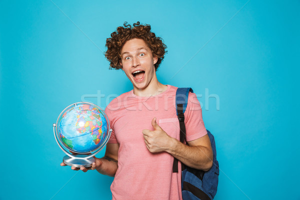 Portrait of european excited guy with curly hair wearing backpac Stock photo © deandrobot