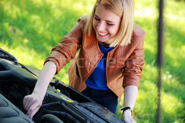 Cheerful woman checking her car engine Stock photo © deandrobot