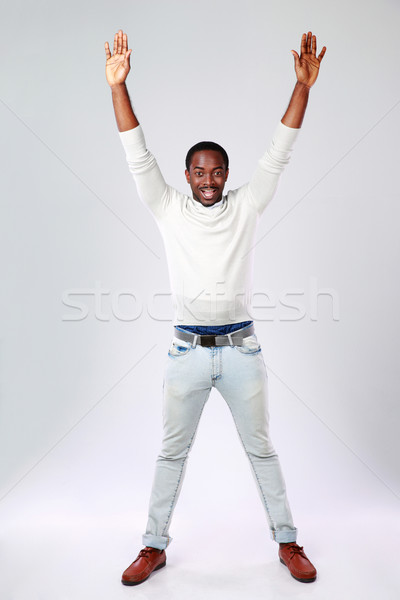 Full length portrait of african man with raised hands on gray background Stock photo © deandrobot