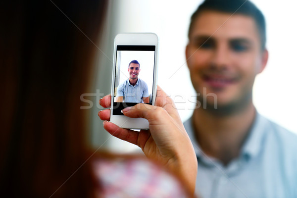 Woman making photo of a man on smartphone. Focus on smartphone Stock photo © deandrobot